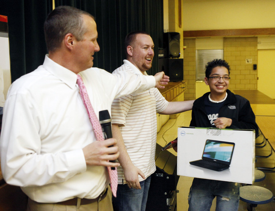 Photo - Principal Brad Herzer (left) and Assistant Principal Joey Slate hand a computer to Armando Selva as they raffle off electronics and prizes to students who attended extra Spring Break classes at Webster Middle School in Oklahoma City, OK, to catch up on their studies, Friday, March 16, 2012,  By Paul Hellstern, The Oklahoman