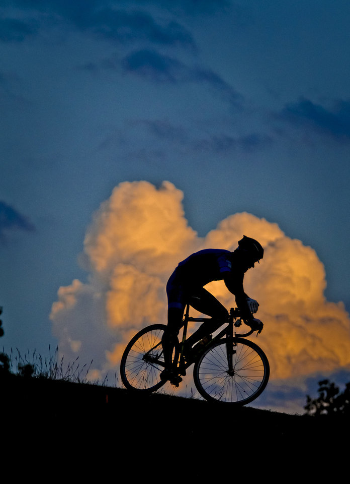 Brandon Melott is silhouetted against a cloud as he races on the cyclocross course near Will Rogers Park during the Oklahoma Cyclocross practice night in Oklahoma City, Okla., on Wednesday, Sept. 19, 2012. Photo by Chris Landsberger, The Oklahoman