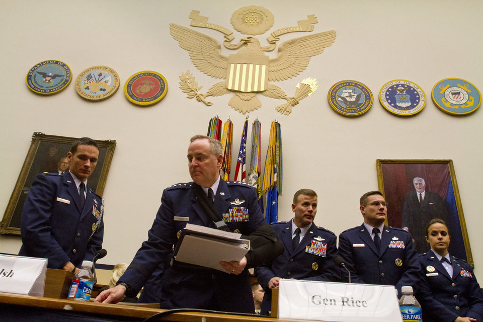 Photo - Air Force Chief of Staff Gen. Mark Welsh III, second from left, picks up papers during a break in his testimony on Capitol Hill in Washington, Wednesday, Jan. 23, 2013, before the House Armed Services Committee hearing on sexual misconduct by basic training instructors at Lackland Air Force Base in Texas. (AP Photo/Jacquelyn Martin)