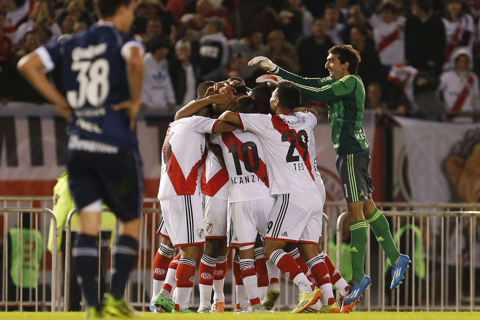 Photo - River Plate players, center, gather around teammate Cristian Ledesma, center, after he scored against Quilmes during an Argentine league soccer match in Buenos Aires, Argentina, Sunday, May 18, 2014. (AP Photo/Victor R. Caivano)