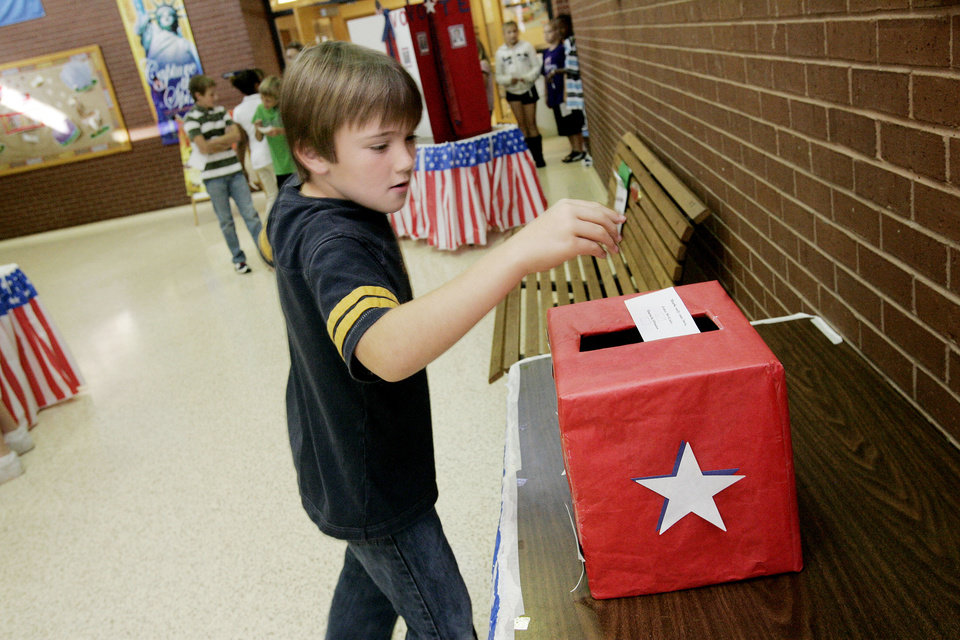Photo - Truman elem. student John Bullard 10 drops his vote in the box during a mock election on Tuesday, Nov. 4, 2008. BY JACONNA AGUIRRE, THE OKLAHOMAN.
