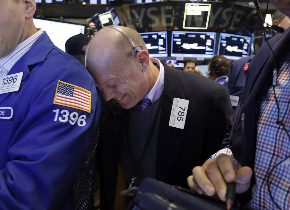 Photo - Trader Daniel Leporin rests his head on a specialist's shoulder as he works on the floor of the New York Stock Exchange Friday, Aug. 1, 2014.  U.S. markets steadied on Friday a day after a major sell-off. Investors focused on a relatively strong jobs report, which showed the U.S. economy created 209,000 jobs in July, the sixth straight month of job growth above 200,000. (AP Photo/Richard Drew)