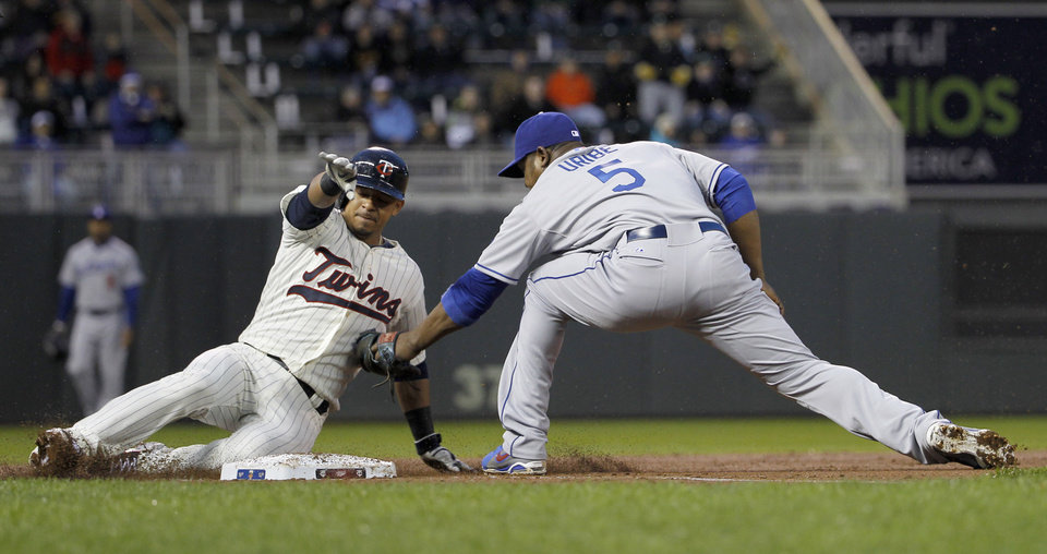 Photo - Minnesota Twins' Eduardo Escobar, left, slides into the tag by Los Angeles Dodgers third baseman Juan Uribe, right, and is out at third while attempting to stretch a double into a triple during the second inning of a baseball game in Minneapolis, Wednesday, April 30, 2014. (AP Photo/Ann Heisenfelt)