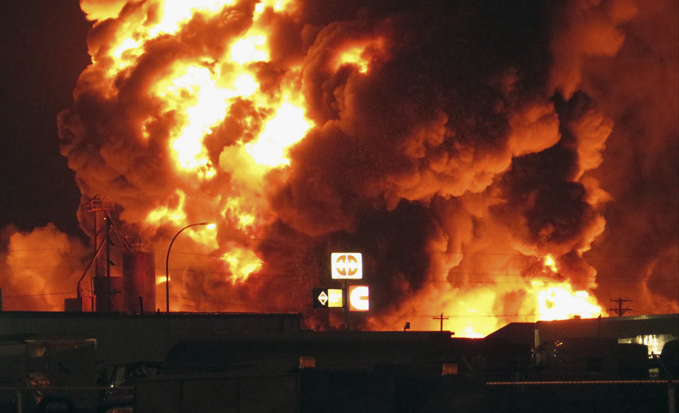 Photo - A fire burns in an industrial part of Williston, N.D. in the early hours of Tuesday, July 22, 2014. The site is near three oil companies and a rail line, just east of Williston's downtown. Explosions could be seen and heard at the scene. Police attributed them to barrels but didn't immediately say what was in them.  No injuries were immediately reported.  (AP Photo/Josh Wood)