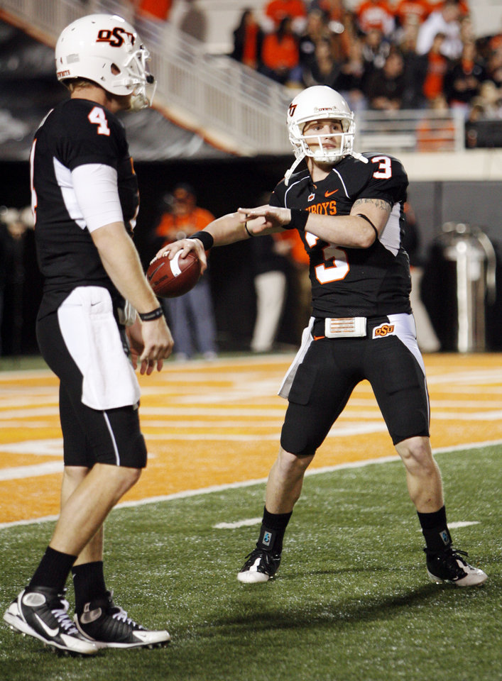 Photo - OSU's Alex Cate (3) warms up next to Brandon Weeden (4) before the college football game between Oklahoma State University (OSU) and the University of Colorado (CU) at Boone Pickens Stadium in Stillwater, Okla., Thursday, Nov. 19, 2009. Photo by Nate Billings, The Oklahoman