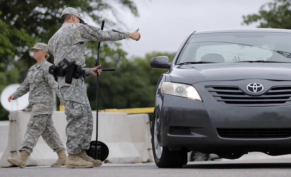 Photo - A driver gets the thumbs-up at a security checkpoint to enter the Lawrence William Judicial Center as the sentencing phase for Maj. Nidal Hasan continues, Tuesday, Aug. 27, 2013, in Fort Hood, Texas. Hasan was convicted of killing 13 of his unarmed comrades in the deadliest attack ever on a U.S. military base. (AP Photo/Eric Gay)