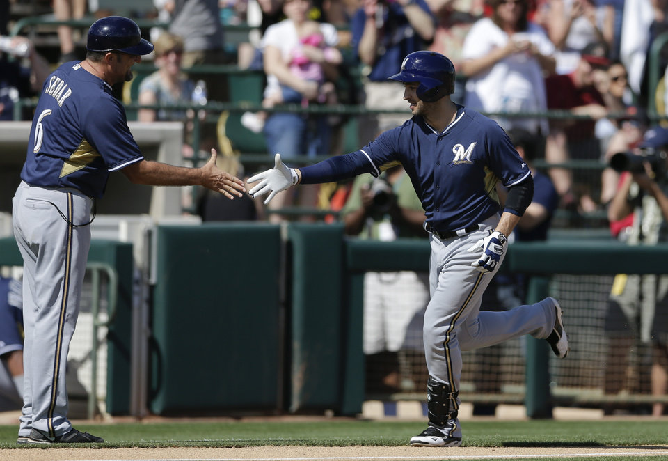Photo - Milwaukee Brewers' Ryan Braun, right, is greeted by third base coach Ed Sedar after hitting a home run during the first inning of a spring training baseball game against the Oakland Athletics, Thursday, Feb. 27, 2014, in Scottsdale, Ariz. (AP Photo/Gregory Bull)