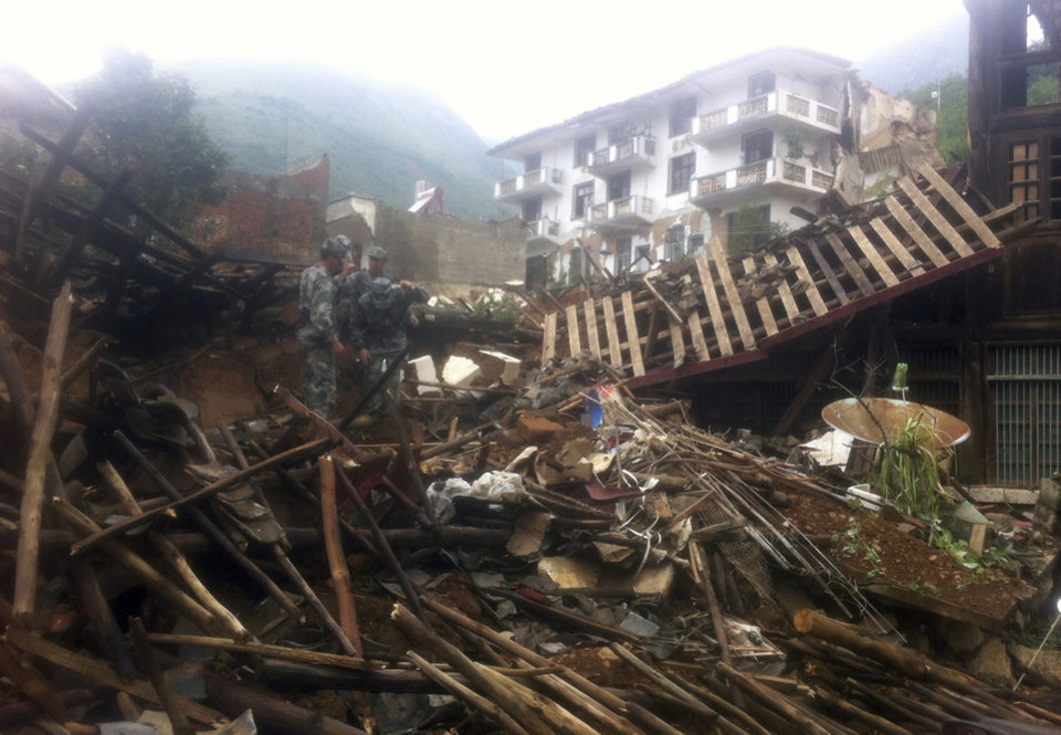Photo - Rescue workers search for survivors in the epicenter of an earthquake that struck the town of Longtoushan in Ludian county in southwest China's Yunnan province Monday, Aug. 4, 2014.  Rescuers dug through shattered homes Monday looking for survivors of a strong earthquake in southern China's Yunnan province that toppled thousands of homes on Sunday, killing hundreds and injuring more than a thousand people. (AP Photo) CHINA OUT
