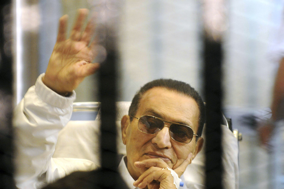 Photo - FILE - In this Saturday, April 13, 2013 file photo, former Egyptian President Hosni Mubarak waves to his supporters from behind bars as he attends a hearing in his retrial on appeal in Cairo, Egypt. Officials say an Egyptian court has ordered the release of ex-President Mubarak, but it's not immediately clear whether the prosecutors will appeal the order. (AP Photo, File)