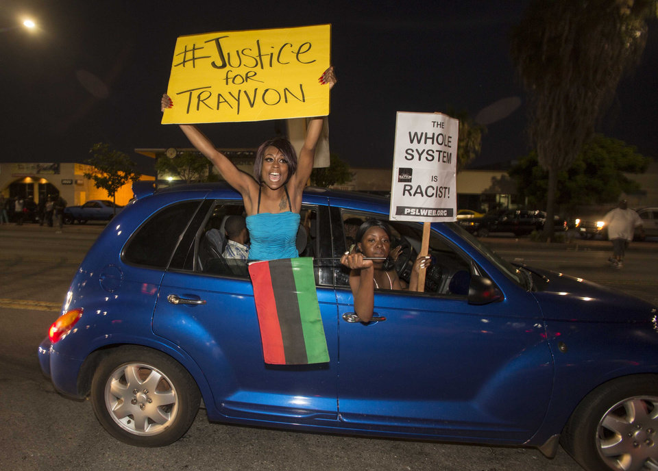 Photo - Demonstrators protest in a car on Crenshaw Boulevard during a protest in Los Angeles on Sunday, July 14, 2013, the day after George Zimmerman was found not guilty in the shooting death of Trayvon Martin. Seventeen-year-old Martin was shot and killed in February 2012 by neighborhood watch volunteer George Zimmerman.  (AP Photo/Ringo H.W. Chiu)
