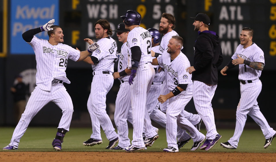 Photo - Colorado Rockies' Nolan Arenado, left, celebrates his walkoff double to drive in two runs with his teammates after the Rockies' 5-4 victory over the San Francisco Giants in a baseball game in Denver on Tuesday, May 20, 2014. (AP Photo/David Zalubowski)