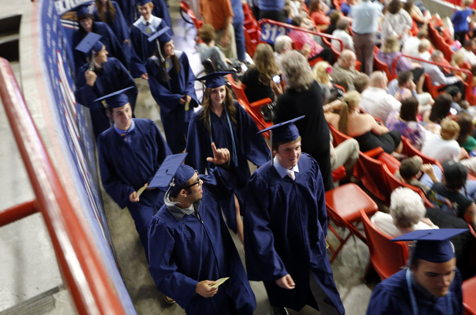 Photo - An Edmond North student waves to his family during graduation ceremonies Saturday at Cox Convention Center. Photo by Sarah Phipps, The Oklahoman  Sarah Phipps - the oklahoman