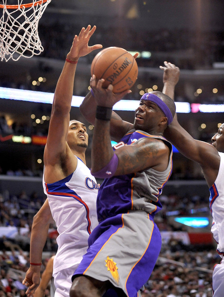 Photo - Los Angeles Clippers center Ryan Hollins, left, and forward Lamar Odom, right, defend as Phoenix Suns center Jermaine O'Neal tries to put up a shot in the first half of an NBA basketball game in Los Angeles on Wednesday, April  3, 2013. (AP Photo/Richard Hartog)