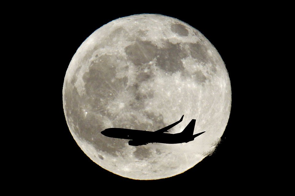 FILE - In this Saturday, Dec. 10, 2011,  file photo, a plane flies over New Jersey with the full moon in the background, in Newark, N.J. The merger of US Airways and American Airlines has given birth to a mega airline with more passengers than any other in the world. (AP Photo/Julio Cortez, File)