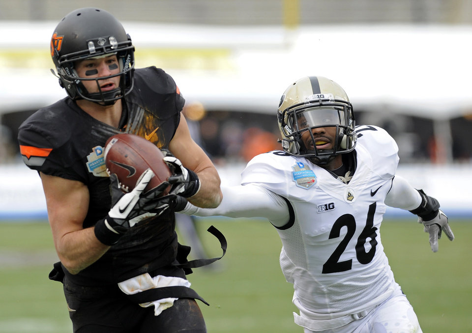 Photo - Oklahoma State wide receiver Charlie Moore makes a catch in front of Purdue cornerback Antoine Lewis (26) during the second half during the Heart of Dallas Bowl NCAA college football game, Tuesday, Jan. 1, 2013, in Dallas. Oklahoma State won 58-14. (AP Photo/Matt Strasen)