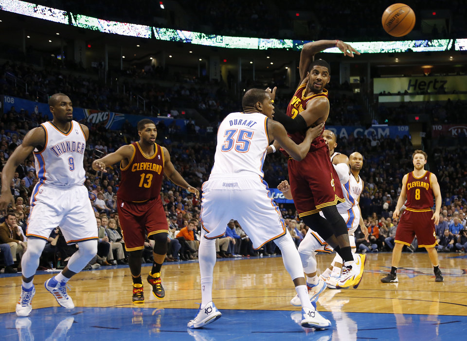 Photo - Cleveland's Kyrie Irving (2) passes the ball in front of Oklahoma City's Kevin Durant (35) during the NBA basketball game between the Oklahoma City Thunder and the Cleveland Cavaliers at the Chesapeake Energy Arena in Oklahoma City, Okla. on Wednesday, Feb. 26, 2014.  Photo by Chris Landsberger, The Oklahoman