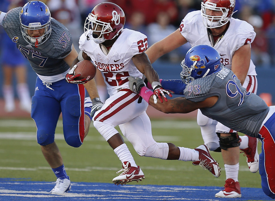 OU's Roy Finch (22) runs between KU's Jake Love (57) and Ben Goodman (93)  during the college football game between the University of Oklahoma Sooners (OU) and the University of Kansas Jayhawks (KU) at Memorial Stadium in Lawrence, Kan., Saturday, Oct. 19, 2013. Oklahoma won 34-19. Photo by Bryan Terry, The Oklahoman