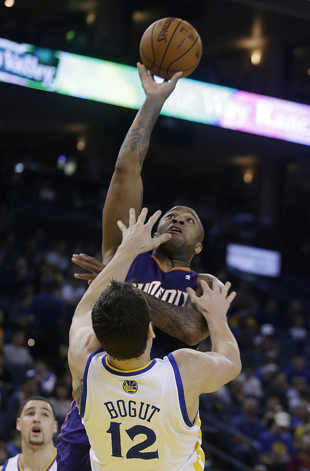 Photo - Phoenix Suns' P.J. Tucker shoots over Golden State Warriors' Andrew Bogut (12) during the first half of an NBA basketball game Sunday, March 9, 2014, in Oakland, Calif. (AP Photo/Ben Margot)