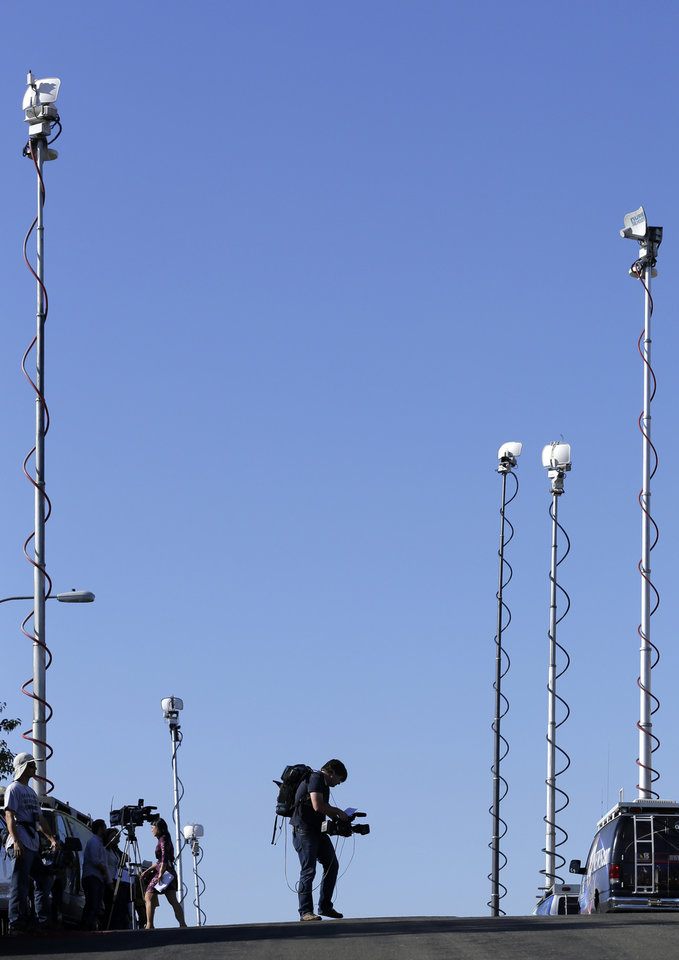 Photo - A videographer works among antenaas from television transmission trucks as reporters wait in front of the home of the mother of Colorado shooting suspect, James Holmes, Friday, July 20, 2012, in San Diego. A gunman in a gas mask barged into a crowded Denver-area theater during a midnight showing of the Batman movie on Friday, hurled a gas canister and then opened fire in one of the deadliest mass shootings in recent U.S. history. (AP Photo/Gregory Bull)  ORG XMIT: CAGB103