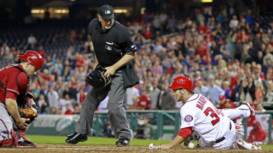 Washington Nationals\' Bryce Harper (34) slides across home plate as Arizona Diamondbacks catcher Miguel Montero loses the ball during the fourth inning of a baseball game, Wednesday, May 2, 2012, in Washington. At center is home plate umpire Bill Welke. (AP Photo/Haraz N. Ghanbari)