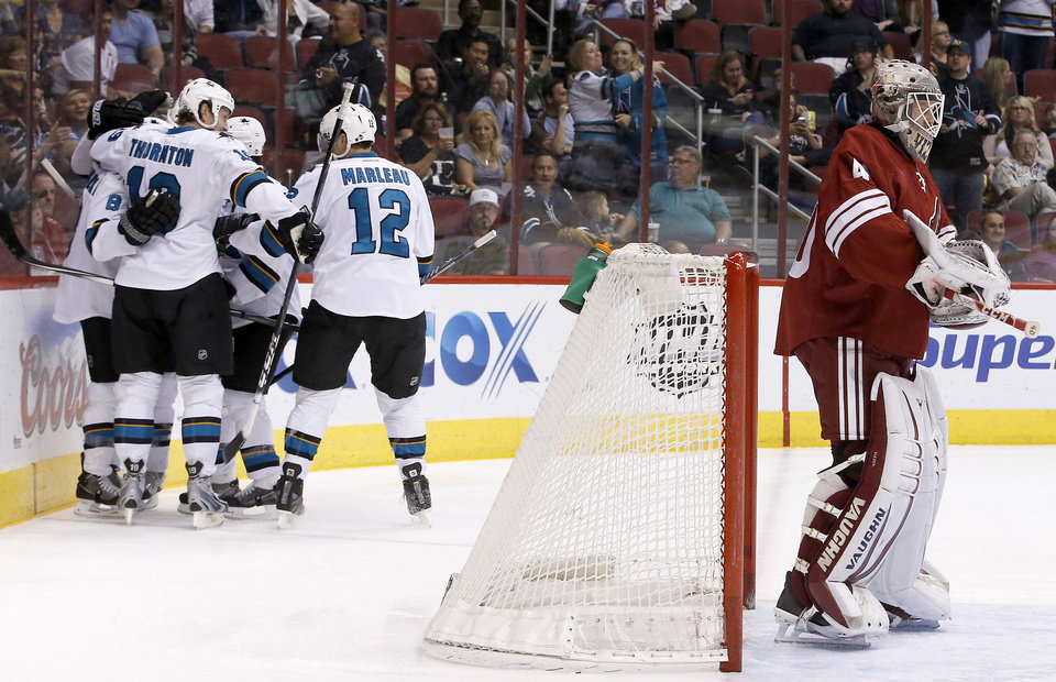 Photo - San Jose Sharks' Joe Pavelski (8) celebrates his goal against Phoenix Coyotes' Mark Visentin, right, with teammates, including Joe Thornton, second from left, and Patrick Marleau (12), during the first period of an NHL hockey game on Saturday, April 12, 2014, in Glendale, Ariz. (AP Photo/Ross D. Franklin)