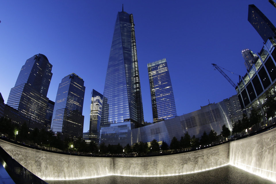 Photo - In this image made with a fisheye lens, One World Trade Center, center, rises above waterfalls at the National September 11 Memorial and Museum, Sunday, Sept. 8, 2013, in New York. Twelve years after terrorists destroyed the old World Trade Center, the new World Trade Center is becoming a reality, with a museum commemorating the attacks and two office towers where thousands of people will work set to open within the next year. (AP Photo/Mark Lennihan)