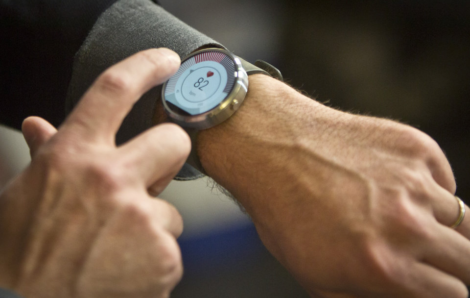 Photo - Steve Sinclair, Motorola's vice president of product management, demonstrates the new Moto 360 circular smartwatch, the company's first, during an interview, Wednesday Aug. 27, 2014 in New York.  (AP Photo/Bebeto Matthews)