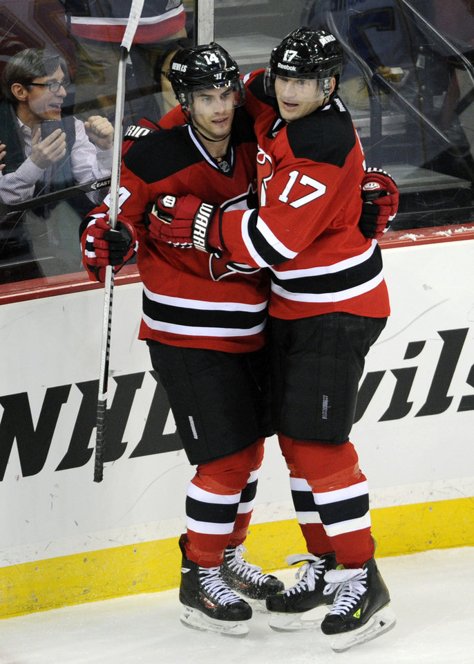 Photo - New Jersey Devils' Adam Henrique, left, celebrates with Michael Ryder after Henrique scored during the second period of an NHL hockey game against the St. Louis Blues Tuesday, Jan. 21, 2014, in Newark, N.J. (AP Photo/Bill Kostroun)
