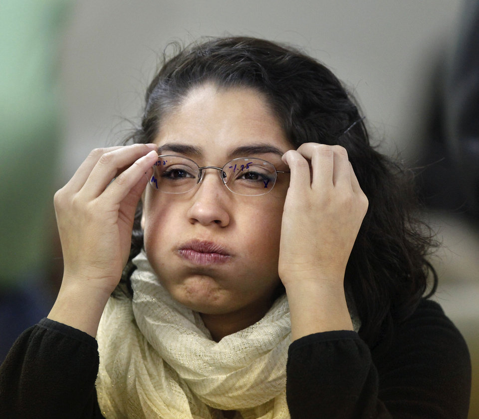 Photo - Ilse Zapata, 18, squints to read the eye chart as she tries on a  pair of glasses. Zapata, a senior at U.S. Grant High School in Oklahoma City, received her first pair of glasses at the free eye clinic. Photo by Jim Beckel, The Oklahoman  Jim Beckel - THE OKLAHOMAN