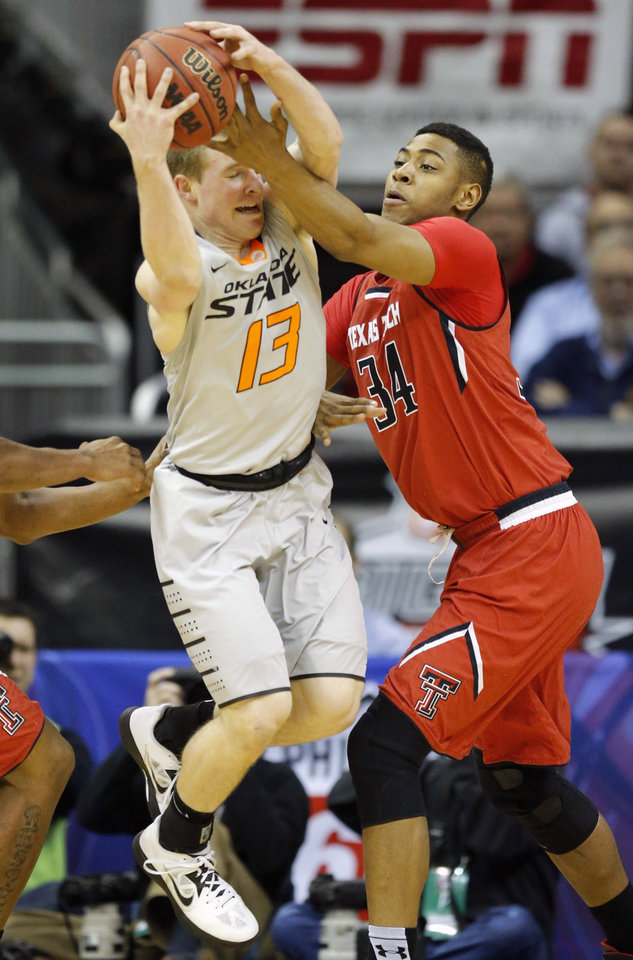 Photo - Oklahoma State guard Phil Forte III (13) rebounds against Texas Tech forward Alex Foster (34) during the first half of their NCAA college basketball game in the Big 12 men's tournament in Kansas City, Mo., Wednesday, March 12, 2014. (AP Photo/Orlin Wagner)
