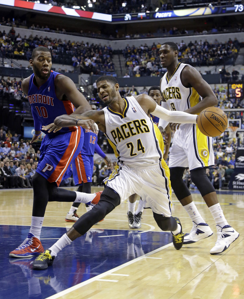 Photo - Indiana Pacers forward Paul George (24) cuts in front of teammate Ian Mahinmi, and Detroit Pistons forward Greg Monroe in the second half of an NBA basketball game in Indianapolis, Monday, Dec. 16, 2013. The Pistons defeated the Pacers 101-96. (AP Photo/Michael Conroy)