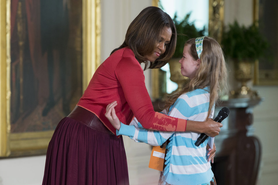 Photo - First lady Michelle Obama hugs Charlotte Bell, 10, after she handed Mrs. Obama her dad's resume during the White House's annual