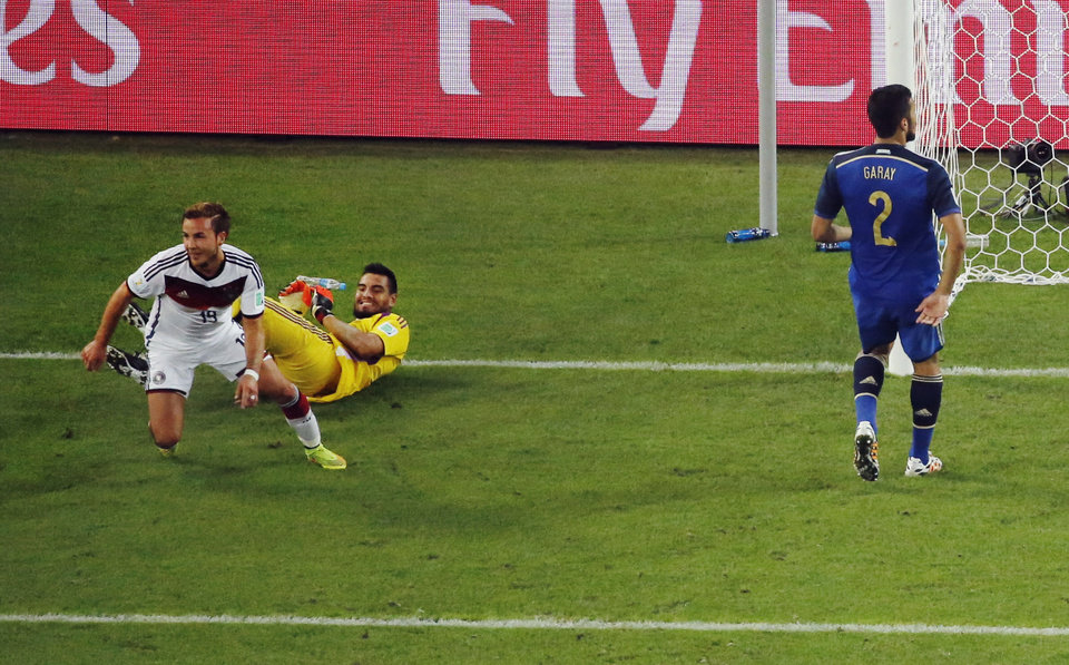 Photo - Germany's Mario Goetze celebrates past Argentina's goalkeeper Sergio Romero after scoring his side's first goal during the World Cup final soccer match between Germany and Argentina at the Maracana Stadium in Rio de Janeiro, Brazil, Sunday, July 13, 2014. (AP Photo/Fabrizio Bensch, Pool)