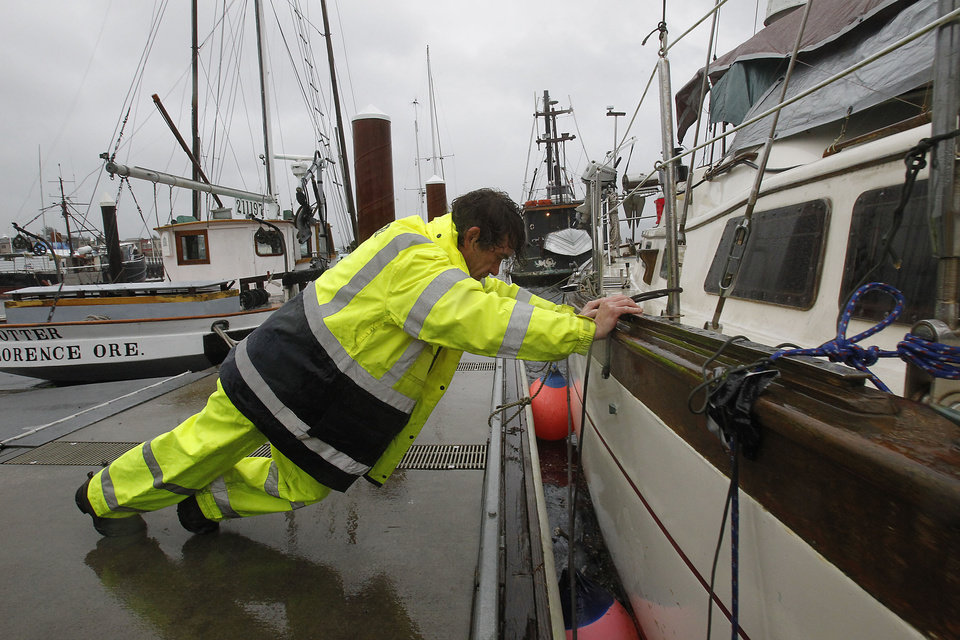 Hugh Oberg pushes his boat so he can put a cushion in between his boat and the dock during a storm in Florence, Ore., Monday, Nov. 19, 2012. High winds were forcing his boat to rub against the dock. (AP Photo/The Register-Guard, Kevin Clark)
