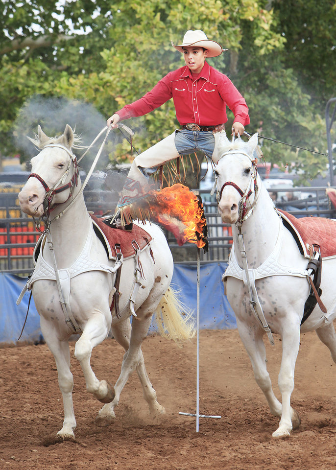Zayne Goode, 13, rides Roman stile over a flaming torch during the Wild West Showcase on the opening day of the 2011 Oklahoma State Fair, Thursday, September 15, 2011. Photo by David McDaniel, The Oklahoman