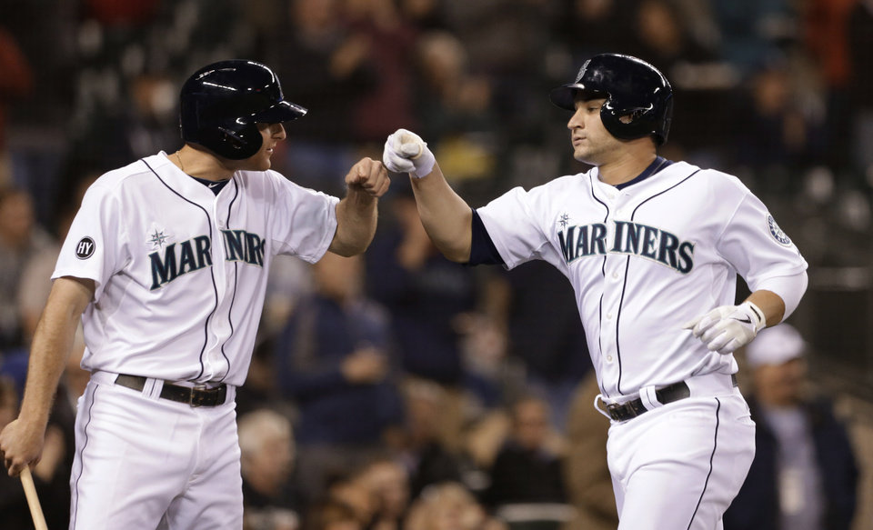 Photo - Seattle Mariners' Mike Zunino, right, is congratulated by Brad Miller on Zunino's home run against the Kansas City Royals in the fifth inning of a baseball game Wednesday, Sept. 25, 2013, in Seattle. (AP Photo/Elaine Thompson)
