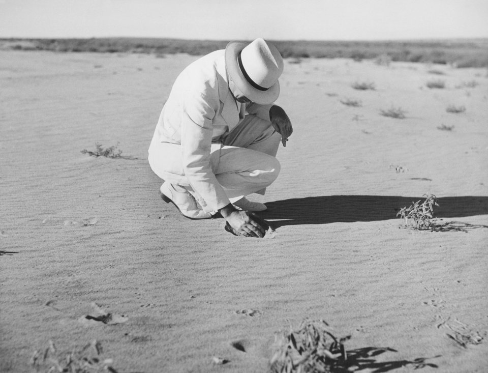 H.H. Bennett, Chief of the Soil Conservation Service and member of President Roosevelt\'s Drought Commission, inspects a dust buried truck on an abandoned farm near Guymon in 1936. AP PHOTO