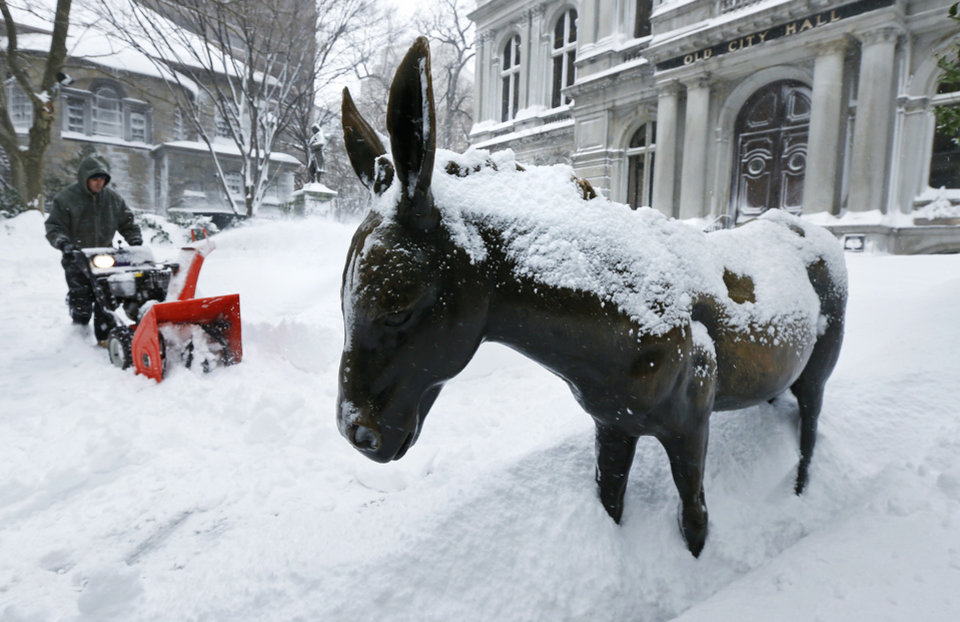 Photo - A worker clears as he passes a snow-covered donkey statue outside Old City Hall in Boston, Saturday, Feb. 9, 2013. The Boston area received about two feet of snow from a winter storm. A howling storm across the Northeast left the New York-to-Boston corridor shrouded in 1 to 3 feet of snow Saturday, stranding motorists on highways overnight and piling up drifts so high that some homeowners couldn't get their doors open. More than 650,000 homes and businesses were left without electricity. (AP Photo/Charles Krupa)