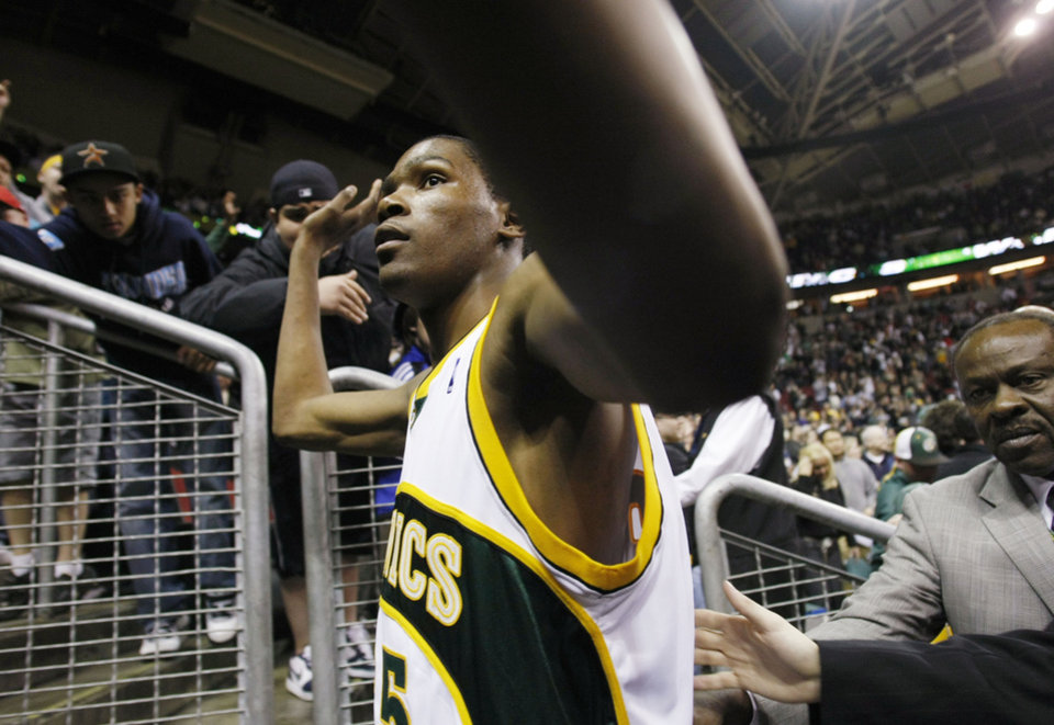 Photo - SEATTLE SONICS: Seattle SuperSonics' Kevin Durant reaches up to fans as he walks from the court after the team's final NBA basketball game of the season, against the Dallas Mavericks in Seattle on Sunday, April 13, 2008. Big-name billionaires of basketball, pressure politics and broken promises have Seattle on the brink of losing its 41-year-old NBA team. The names involved include Starbucks chairman Howard Schultz, Microsoft CEO Howard Ballmer and Oklahoma financial capitalist Clay Bennett. Despite so many efforts to keep the team from leaving, the NBA is set to approve the Sonics' move to Oklahoma City on Friday. (AP Photo/John Froschauer) ORG XMIT: WAJF101