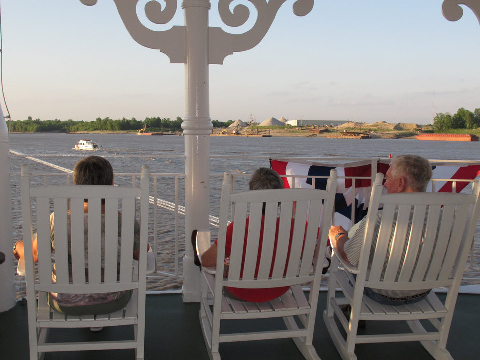 Photo -   In this April 27, 2012 photo, passengers on the American Queen steamboat take in the view as they sit on rocking chairs as the vessel moves up the Mississippi River in Memphis, Tenn. The American Queen is the largest steamboat in the world, carrying 436 passengers. The 418-foot-long vessel is taking tourists on long-distance trips on the Mississippi for the first time since 2008, when its previous owner ceased operations. (AP Photo/Adrian Sainz)