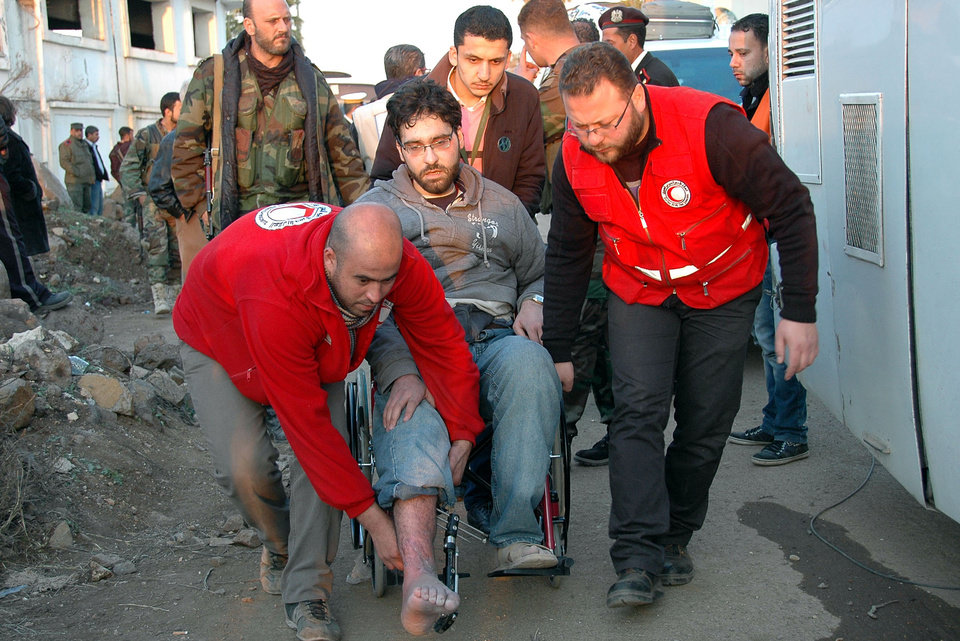 Photo - In this photo taken on Sunday Feb. 9, 2014, and released by the Syrian official news agency SANA, Syrian Arab Red Crescent members in red uniforms help evacuate an injured man on a bus out of the battleground city of Homs, Syria. A Syrian Red Crescent official says around 300 more people were evacuated Monday from besieged rebel-held neighborhoods of Syria's third-largest city, Homs. (AP Photo/SANA)