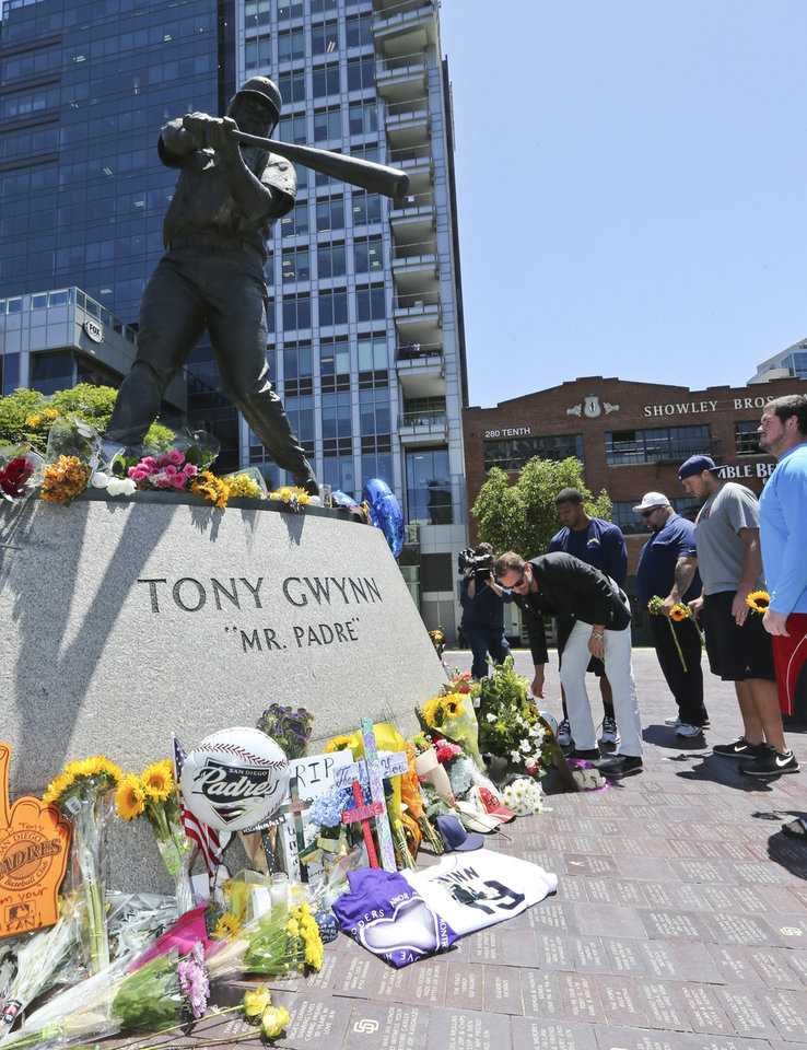 Photo - A.G. Spanos, CEO of the San Diego Chargers, leads his team as they place flowers and other mementos at the base of the Tony Gwynn