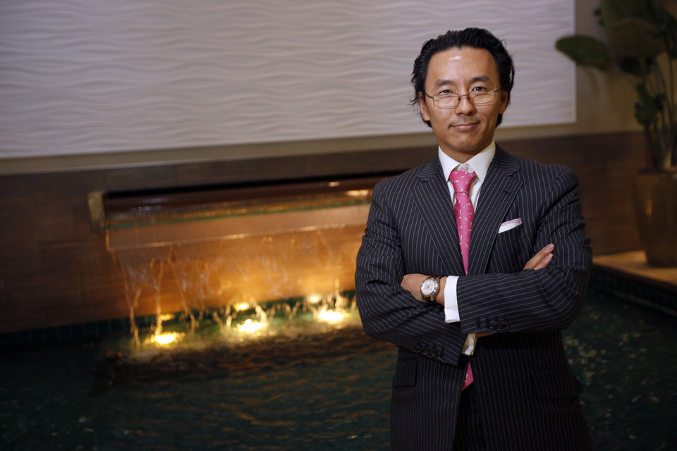 Mukang Cho, Chief Executive Officer and Principal of In-Rel Properties, Inc.,  poses for photo by a fountain at 50 Penn Place in Oklahoma City, Thursday, March 15, 2012. Photo by Sarah Phipps, The Oklahoman.