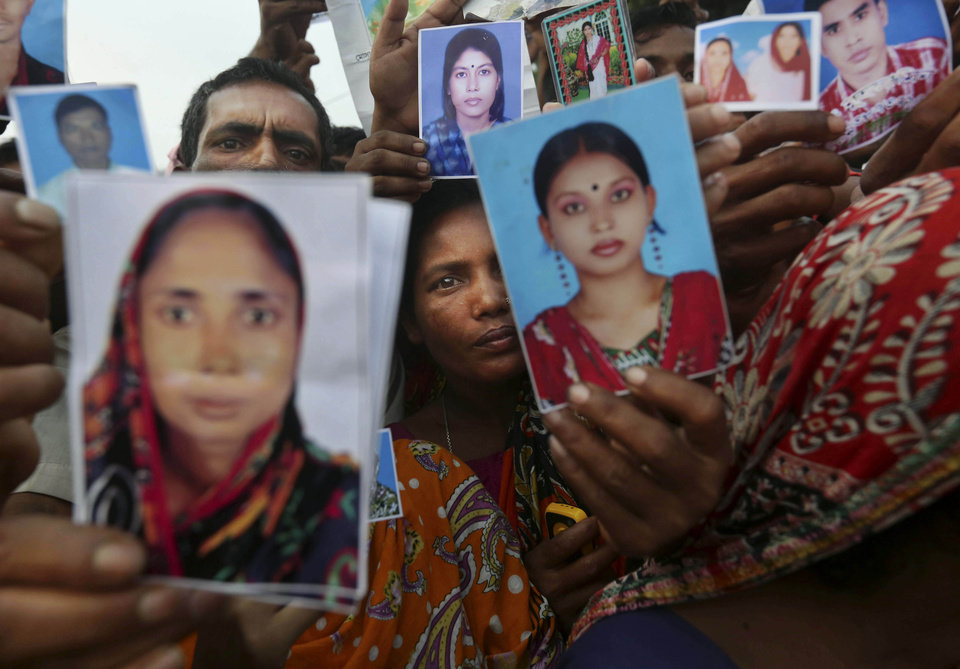 Photo - Bangladeshi relatives of workers missing in a building that collapsed Wednesday hold pictures of loved ones at a makeshift morgue in a schoolyard in Savar, near Dhaka, Bangladesh, Saturday, April 27, 2013. Police in Bangladesh arrested two owners of a garment factory in a shoddily-constructed building that collapsed this week, killing hundreds of people, as protests spread to a second city Saturday with hundreds of people throwing stones and setting fire to vehicles. (AP Photo/Kevin Frayer)