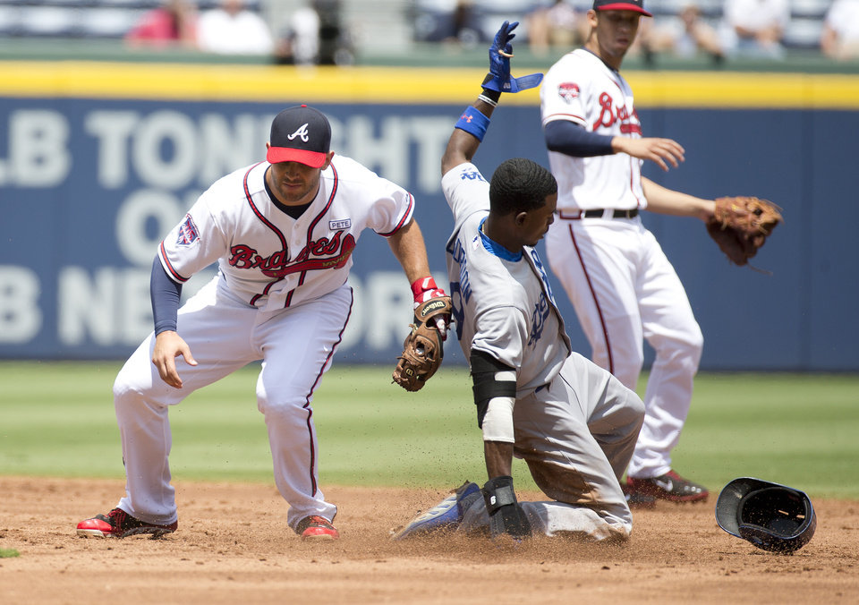 Photo - Los Angeles Dodgers' Dee Gordon (9) steals second base as Atlanta Braves second baseman Tommy La Stella (7) applies the late tag in the third inning of a baseball game Thursday, Aug. 14, 2014, in Atlanta. (AP Photo/John Bazemore)