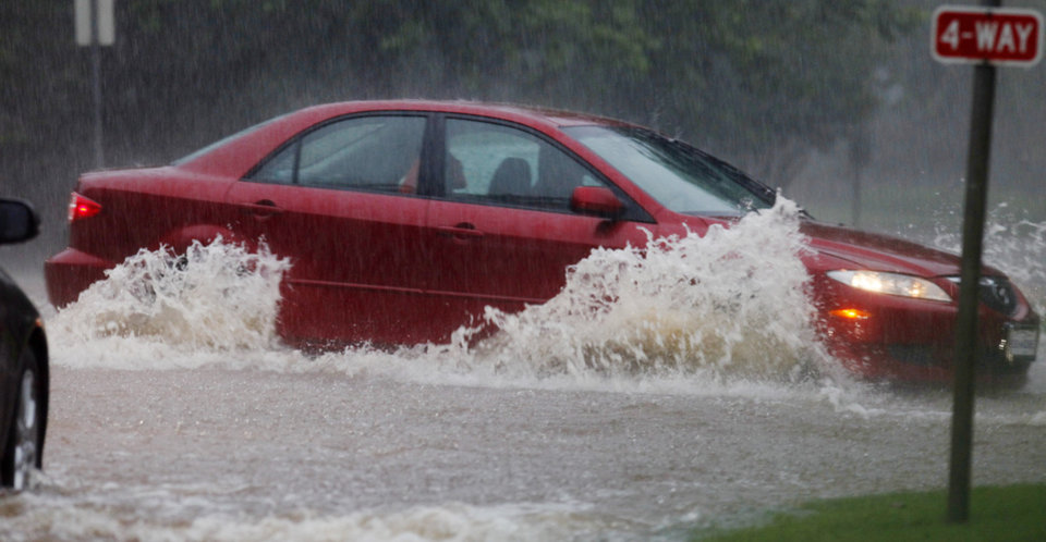 A car tries to make it through high water on Wilshire Blvd. at Nichols Road during heavy rains in Nichols Hills Monday, June 14, 2010. Photo by Paul B. Southerland, The Oklahoman
