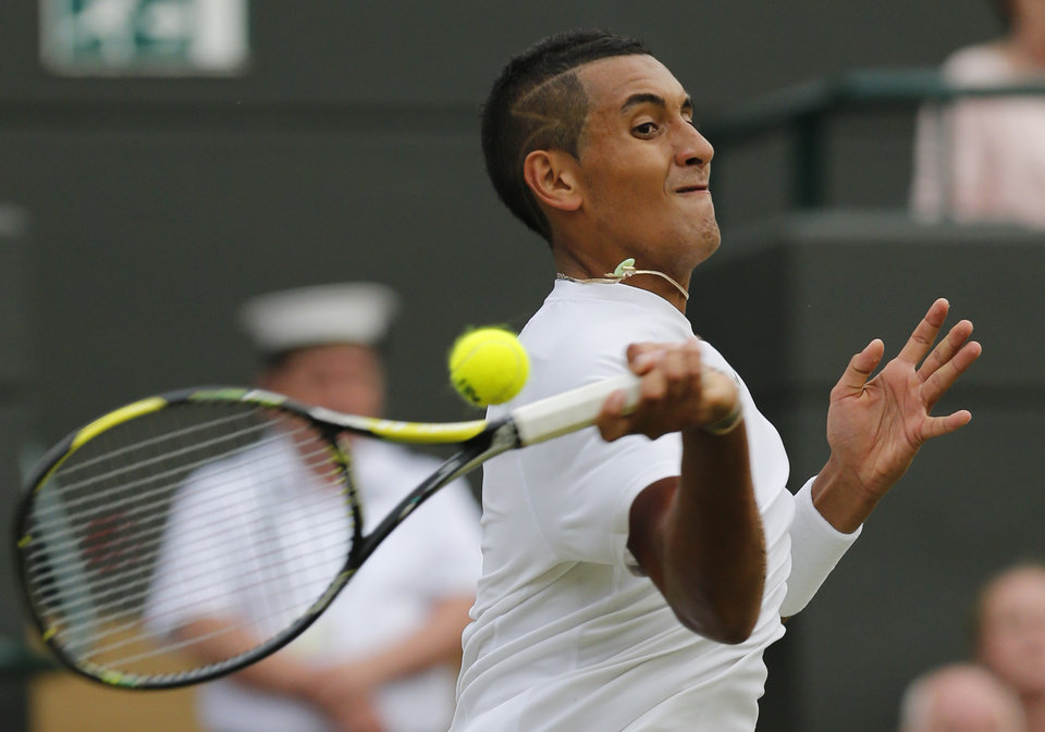 Photo - Nick Kyrgios of Australia returns during the men's singles quarterfinal match against Milos Raonic of Canada at the All England Lawn Tennis Championships in Wimbledon, London, Wednesday, July 2, 2014. (AP Photo/Ben Curtis)