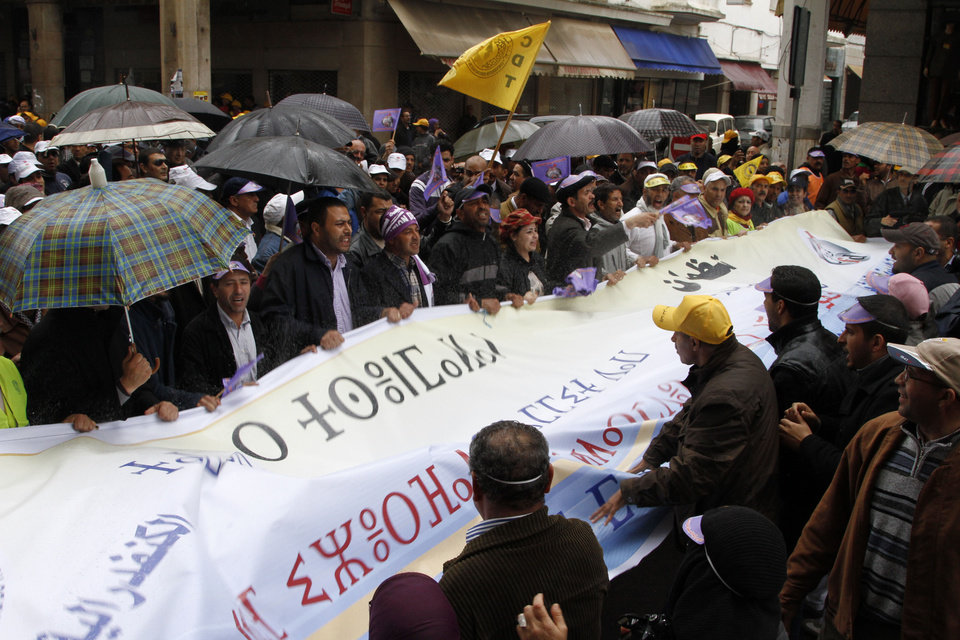 Moroccan union members chant for the fall of the government while holding a banner reading in Arabic and Berber