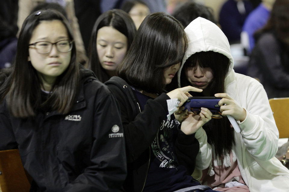 Photo - Students check their mobile phone for the latest news on the ferry that sank Wednesday, which was carrying 475 people aboard, including 325 students,  at an auditorium in Danwon High School in Ansan, South Korea, Thursday, April 17, 2014. Strong currents, rain and bad visibility hampered an increasingly anxious search Thursday for 287 passengers, many thought to be high school students, still missing more than a day after their ferry flipped onto its side and sank in cold waters off the southern coast of South Korea. (AP Photo/Woohae Cho)