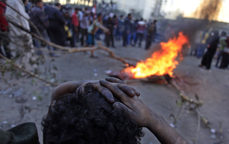 Egyptian protesters set up fire during clashes with riot police, not seen, near Tahrir Square, Cairo, Egypt, Friday, Jan. 25, 2013. Two years after Egypt's revolution began, the country's schism was on display Friday as the mainly liberal and secular opposition held rallies saying the goals of the pro-democracy uprising have not been met and denouncing Islamist President Mohammed Morsi. With the anniversary, Egypt is definitively in the new phase of its upheaval.  (AP Photo/Khalil Hamra) ORG XMIT: KH118